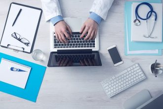 doctors hands usng a laptop on a desk with other medical admin files