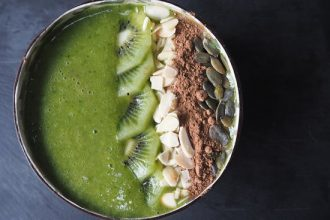 Close up picture of a green smoothie in a coconut bowl topped with slices of kiwi, flaked almonds, cacoa powder and pumpkin seeds