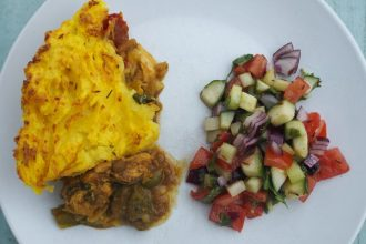 White plate with yellow mashed potato on top of chunks of chicken in a jalfrezi sauce and a mixed dressed salad