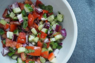 Light brown bowl filled with chopped cucumber, tomatoes, red onions, herbs and dressed with indian spices