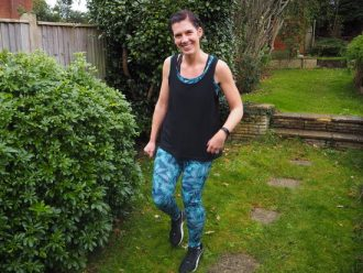 Smiling dark haired girl in graden next to a bush, wearing tropical blue leggings and black vest top
