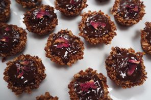 lots of small brown flapjacks covered in chocolate and decorated with rose petals