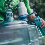 Close up picture of a person filling up a water bottle from a large clear cannister