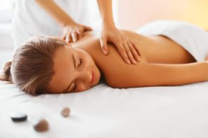 Female lying down with exposed shoulders receiving a massage from a therapiste