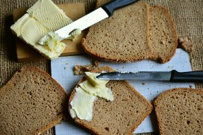 6 slices of brown bread on a chopping board wit two knives spreading lots of butter