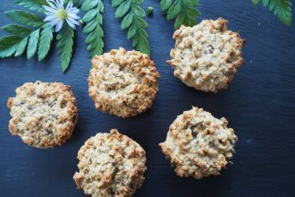 5 round flapjacks beside a fern leaf and 1 purple daisy head with a dark grey slate background