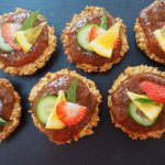 6 round flapjacks topped with Pimms strawberry jam and decorated with sliced strawberry, lemon, cucumber and mint leaf, on a dark grey slate background