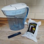 Water filter jug, filter cartidge in sealed plastic wrapping and a water meter test stick all sat on a wooden kitchen worktop with cream rectangular tiles on background