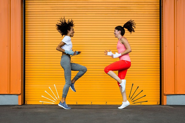 Two ladies in their early thirties dressed in fitness gear high knee running on the spot. Yello lined background, one on right wearing 3/4 length red leggings, pink vest top. One on left wearing full length mid grey leggins and a white t-shirt. Trying to increase their metabolism