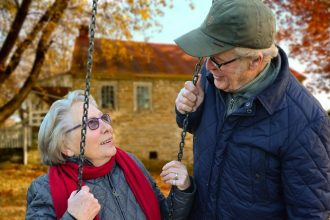 Older lady sat on a swing smiling up at an older man wearing a hat
