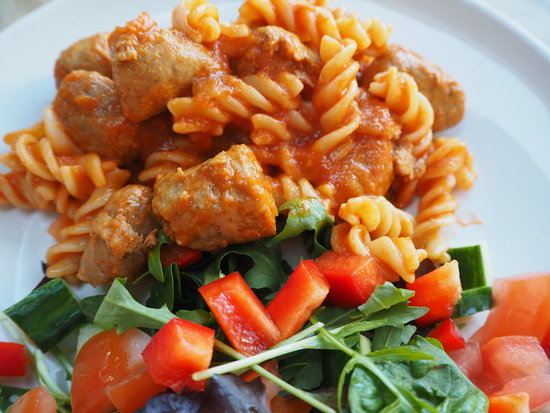 Close up of pasta twirls in tomato sauce with sausage meatballs and a side salad