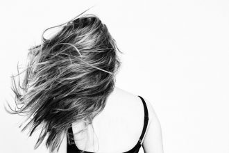Black and white image of the back of a femaile with long hair being flicked out to the side.