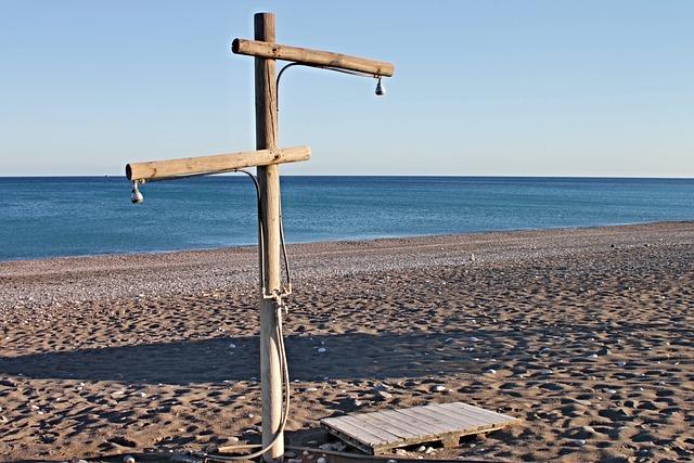 Wooden shower post on a hot beach