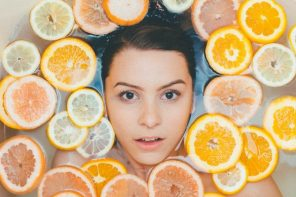 Woman's face submerged in water, surrounded by slices of orange and lemon to indicate she has a healthy eco friendly bathroom