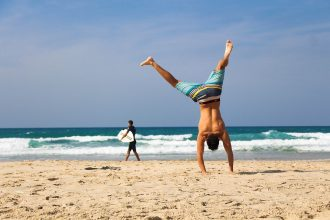Man on a beach doinga handstand, man in the background holding a surfboard