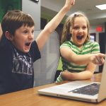 young boy and girl sat in front of an open laptop. Boy is cheering and girl is pointing at the screen and laughing. controversial subject matter perhaps.