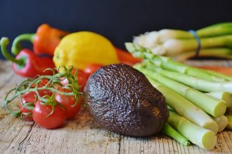 Selection of vegetables on a wooden chopping board demonstrating a vegan diet