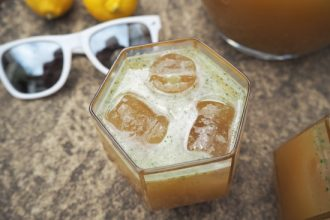 2 lemons, white sunglasses close up of top of glass filled with mint lemonade and 3 ice cubes