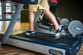 Image of man running on a treadmill fromt eh waist down, focusing on his feet