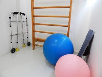 White room containing physical therapy equipment including a blue and pink exercise balls and walking frames