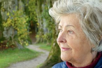 Old lady staring into the distance in outdoor park looking as if she has dementia