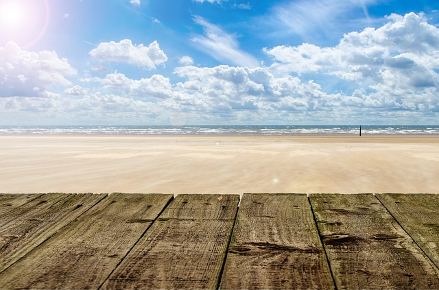 Beach - golden sand with sea on the horizon and bright blue sky filed with fluffy clouds