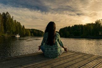 Long haired brunette lady sat crosslegged at the end of a pier overlooking a lake practising mindfulness