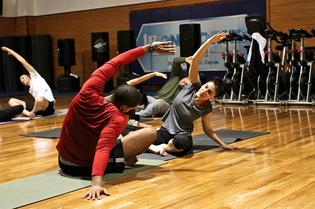 Couple sat facing each other in a gym, stretching to the side with their arms. Displays how exercising together can fomr intimate relationships