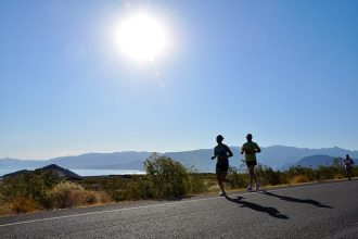 two people running on a road alongside a beach on a hot day. they're wearing shorts and likely to be suffering from thigh chafing in the hot weather.