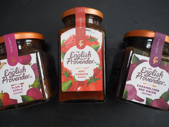 Three jars of The English Provender Co. chutneys and pickle laid down on a dark slate background