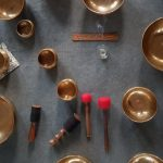 A range of Tibetan singing bowls use for sound therpay and meditation positioned on a grey carpet