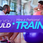 Male personal trainer assisting a female doing sit ups sat on a blue exercise ball