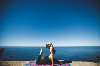 Female in lycra practising yoga on a cliffside overlooking the ocean and beautiful clear blue sky