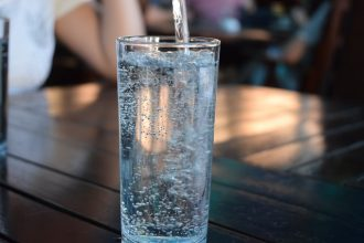 Tall glass filled with water sat on a table