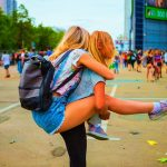 two blonde haired girls having fun at a summer festival. One is giving the other a piggy back.
