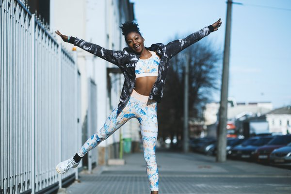 Young black female doing half a star jump, wearing sports gear and happy she's found the right workout plan
