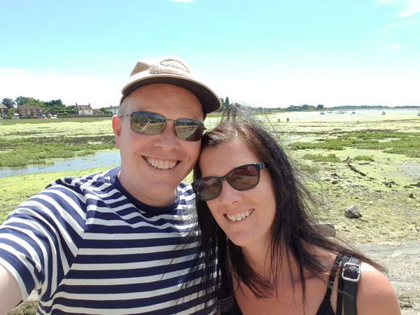 Headshot of male and female wearing sunglasses smiling with beautiful natural harbour in the background. The picture of a healthy happy relationship