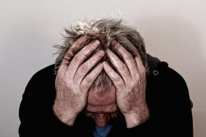older man holding his head in his hands trying to relieve a headache