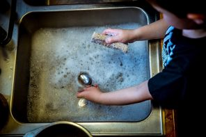 Close up of young boys arms, sleeves rolled up stood at a sink doing the washing up. Cutlery and sponge in hands with bubbly water in silver sink. Showing children should be using natural products.