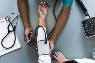 Close up of the arms of a patient and doctor taking blood pressure results - health and genetic testing
