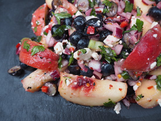Close up of Chilli, Peach and Blueberry Salad served on a dark grey slate