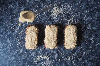 Three rectangular sesame seed flapjacks lined up in a row on a dark grey mottled kitchen worktop. Sesame seeds have been scattered around it and there is a teaspoon overspilling with tahini just above the flapjacks on the worktop.