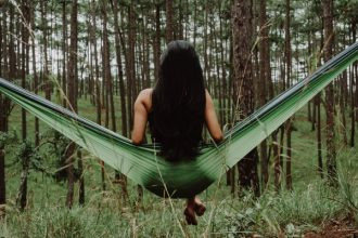 back of a long haired brunnet lady sat on a green hammock in the middle of a forest