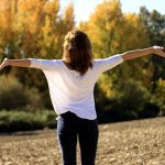 Back of dark haired lady with her arms outstretched breathing in the natural air outside helping to relieve her asthma