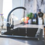 Black sink in a kitche n with middle black tap puring water into sink. Water filtration