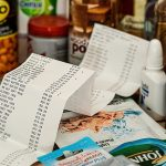 Close up of grocery food shopping with a receipt in front of it, signifying healthy food on a budget