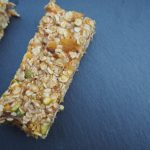 Rectangular no bake vegan date abd aoricot flapjack presented on a dark grey slate board