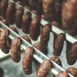 Three rows of smoked sausages hanging on smoking racks