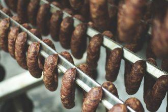 Three rows of smoked sausages hanging on smoking racks