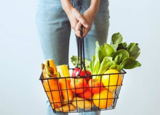 shopping basket filled with brightly coloured fruits and vegetables being held by a woman. You can only see her hand and jeans from waist down to knees